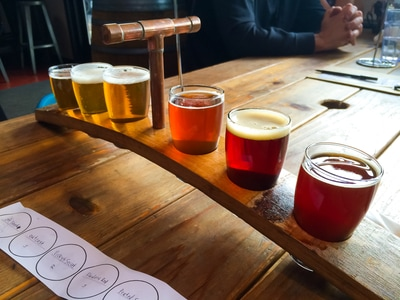 A flight of beers sits at the ready for someone to taste
