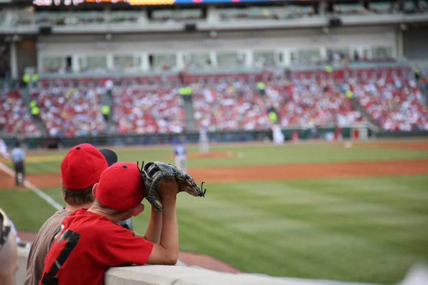 Two boys watching a baseball game from the front row in right field