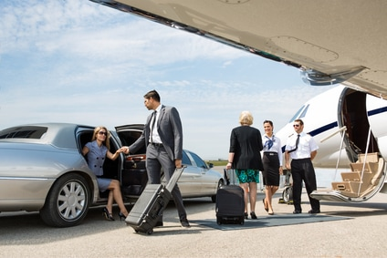 Chauffeur meeting corporate executives at their limo and helping to transport luggage to a private jet at the airport