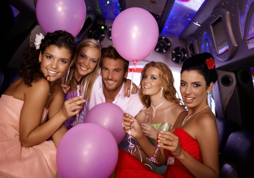 A group of young partiers celebrating a birthday party in a luxurious limousine
