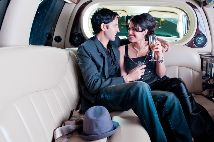 Couple enjoying a glass of champagne in the back of a limo while riding to their favorite restaurant