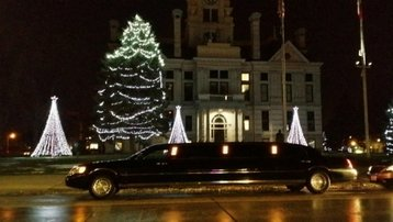 Stretch black Lincoln Towncar parked outside a beautifully lit building decorated with Christmas lights