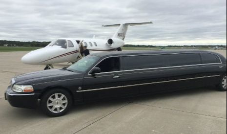 Our stretch black Lincoln Towncar parked on the tarmac next to a private jet at the Des Moines airport