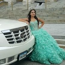 Girl celebrating her quinceañera and leaning against a white Cadillac Escalade parked in front of a building in downtown Des Moines