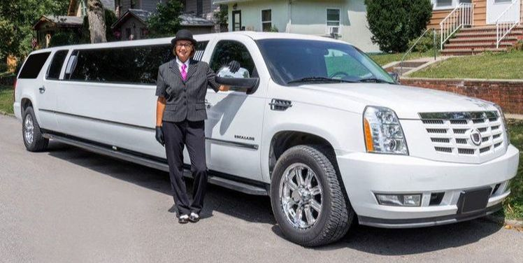 15 passenger stretch Cadillac Escalade with a chauffeur standing next to it