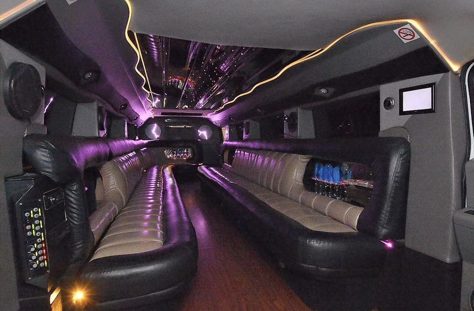 Picture of the inside of a gray stretch Hummer H2 showing mirrored ceiling, premium leather bench seating, wooden floor, rope and LED lighting