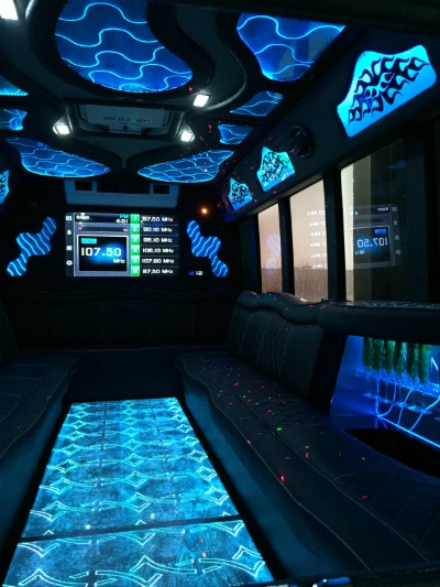 Amazing interior picture of 22 passenger limo bus with custom, color changing lighting and disco floor. A large flat panel DirecTV connected TV is visible on the back wall.